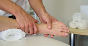 Physiotherapist giving foot massage to a female patient stock footage