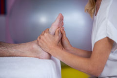 Physiotherapist giving foot massage to a patient stock photography