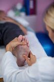 Physiotherapist giving foot massage to a patient Stock Images