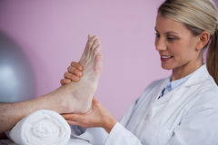 Physiotherapist giving foot massage to a patient Royalty Free Stock Image
