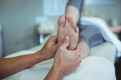 Physiotherapist giving foot massage to a woman Stock Photo
