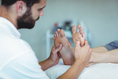 Physiotherapist giving foot massage to a woman Stock Photos
