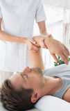 Physiotherapist giving hand massage to man Stock Image