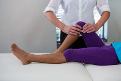 Physiotherapist giving leg massage to a girl patient. In clinic Stock Images
