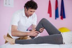 Physiotherapist giving leg massage to a senior woman Stock Image