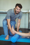 Physiotherapist giving leg massage to a woman on exercise mat Royalty Free Stock Photos