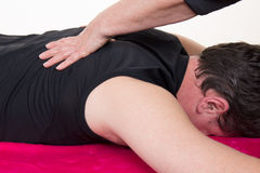 Physiotherapist giving male patient massage Stock Photos
