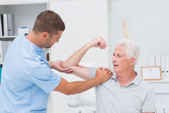 Physiotherapist giving massage to senior man Stock Image