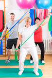 Physiotherapist giving patients gymnastic exercise Stock Images