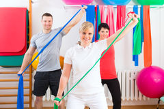 Physiotherapist giving patients gymnastic exercise Stock Photos