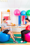 Physiotherapist giving patients gymnastic exercise Royalty Free Stock Photo