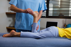 Physiotherapist giving physical therapy to the girl. In hospital Stock Photos