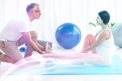Physiotherapist giving physiotherapy to pregnant lady. On exercise mat stock photos
