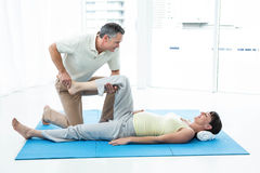 Physiotherapist giving physiotherapy to pregnant woman. Pregnant women exercising her legs with physiotherapist  at home Stock Images