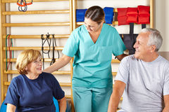 Physiotherapist giving senior rehab. Happy physiotherapist giving senior group rehab classes in gym Stock Photography
