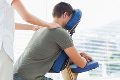 Physiotherapist giving shoulder massage to man Stock Image