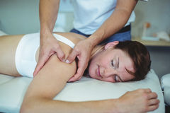 Physiotherapist giving shoulder massage to a woman Royalty Free Stock Images