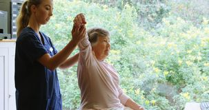 Physiotherapist giving shoulder therapy to senior woman 4k