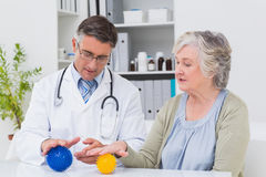 Physiotherapist guiding female patient with massage ball Stock Photo