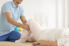 Physiotherapist helping in correct positioning. Of leg during meeting with patient Royalty Free Stock Photography