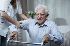 Physiotherapist helping disabled senior man. Physiotherapist helping disabled senior men with standing Royalty Free Stock Images