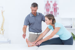 Physiotherapist helping his patient stretching royalty free stock photos
