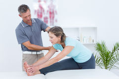 Physiotherapist helping his patient stretching Stock Images
