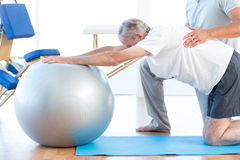 Physiotherapist helping man with exercise ball. Physiotherapist helping men with exercise ball in medical office Royalty Free Stock Images