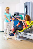 Physiotherapist helping patient retrieve crutches. After performing rehabilitation exercises on weight machine Royalty Free Stock Photo