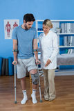 Physiotherapist helping patient to walk with crutches. In clinic Stock Images