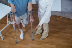 Physiotherapist helping patient to walk with crutches. In clinic Royalty Free Stock Photos