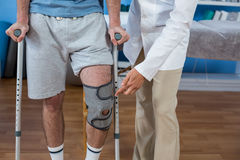 Physiotherapist helping patient to walk with crutches. In clinic Stock Photography