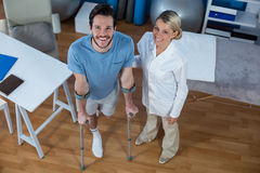 Physiotherapist helping patient to walk with crutches. Portrait of physiotherapist helping patient to walk with crutches in clinic Stock Images