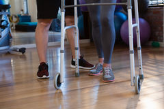 Physiotherapist helping patient to walk with walking frame in clinic. Low section of physiotherapist helping patient to walk with walking frame in clinic Stock Image
