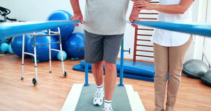 Physiotherapist helping patient walk with parallel bars stock video