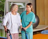 Physiotherapist helping senior stock photography