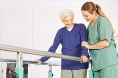 Physiotherapist helping woman on treadmill Stock Image