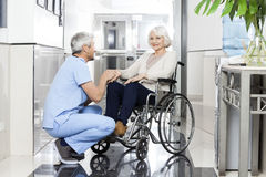 Physiotherapist Holding Smiling Senior Woman's Hand On Wheelchai. Mature male physiotherapist holding smiling senior woman's hand on wheelchair in rehab center Royalty Free Stock Photography