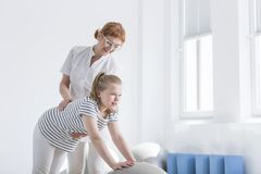 Physiotherapist improving posture of girl. With her hands on a grey ball for corrective exercises Royalty Free Stock Images