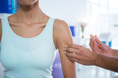 Physiotherapist injecting female patient. In clinic Stock Images