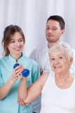 Physiotherapist insuring senior during exercise Stock Images