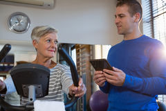 Physiotherapist interacting with senior woman while exercising on exercise bike Stock Image