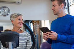 Physiotherapist interacting with senior woman while exercising on exercise bike Stock Images