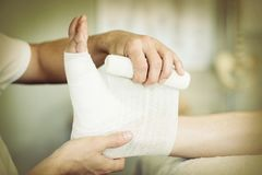 Physiotherapist kładzenia bandaż na zdradzonych ciekach pacjent obraz royalty free