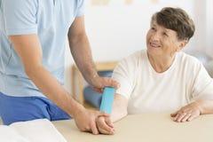 Physiotherapist kładzenia kinesiotape na ręce zdjęcie stock