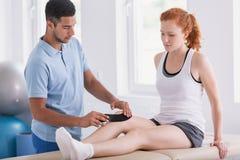 Physiotherapist kładzenia taśmy na pacjent nodze podczas kinesiotaping obraz stock