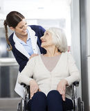 Physiotherapist Looking At Senior Patient Sitting In Wheelchair Royalty Free Stock Photos