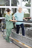 Physiotherapist Looking At Senior Patient Walking Between Bars Royalty Free Stock Photo