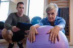 Physiotherapist maintaining record of senior woman performing exercise on fitness ball Royalty Free Stock Photos