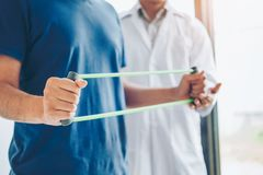 Physiotherapist man giving resistance band exercise treatment About Chest muscles and Shoulder of athlete male patient Physical. Physiotherapist men giving royalty free stock photos
